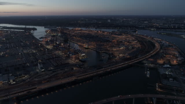 hamburg harbour industrial area at dusk, city skyline, container terminal, river elbe - hafen stock-videos und b-roll-filmmaterial