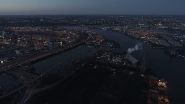 hamburg harbour industrial area at dusk, city skyline with traffic - hafen stock-videos und b-roll-filmmaterial