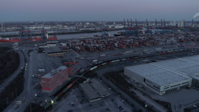 hamburg harbour industrial area at dusk, container train moving, flight towards container terminal - hamburg germany stock videos & royalty-free footage