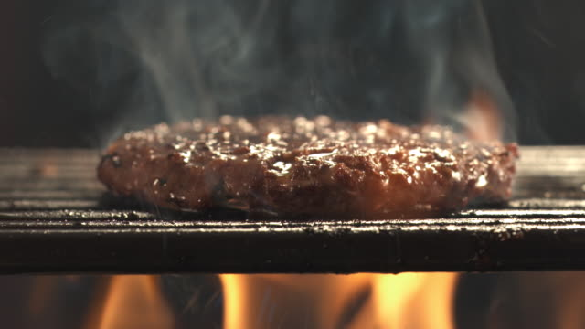 cu hamburger patty on open grill being flame broiled with lot of smoke and slice of plain american cheese being placed on top / los angeles, california, united states - flamme stock-videos und b-roll-filmmaterial