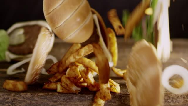 vídeos de stock, filmes e b-roll de slo mo r/f hambúrgueres e batata crocante cunhas caindo sobre uma mesa - frito