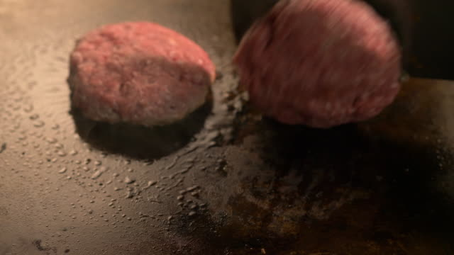 hamburgers patties cooked on a commercial griddle at a diner restaurant - グリルパン点の映像素材/bロール