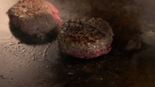 Hamburgers patties cooked on a commercial griddle at a diner restaurant