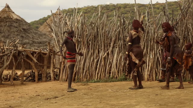 hamer tribe- women provoke a young man at the whipping ceremony, hamer tribe, ethiopia. - ethiopia stock videos and b-roll footage