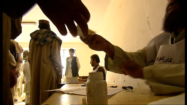 Hamid Karzai agrees to runoff presidential election LIB Close up of voter dipping finger into pot of ink at polling station Ballot papers Man casting...