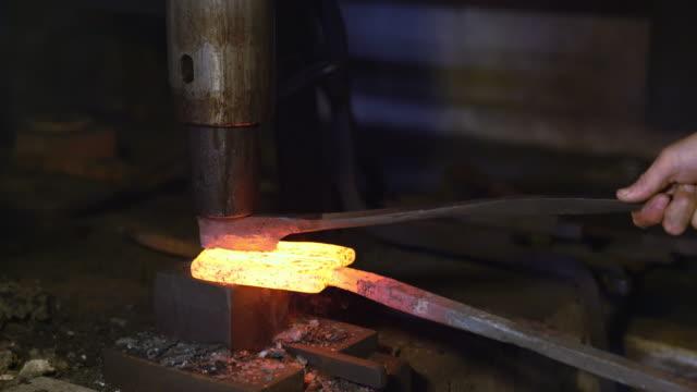 Hammer beating glowing metal bar into shape