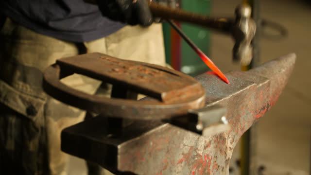 vídeos de stock e filmes b-roll de hammer hits glowing metal object on anvil - ferro metal
