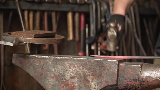 vídeos de stock e filmes b-roll de hammer hits glowing red metal object on anvil - ferro metal