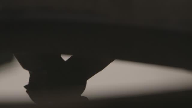 vídeos de stock e filmes b-roll de a hammer is reflected in a bucket of water at a workshop in sierra leone. - ferro metal