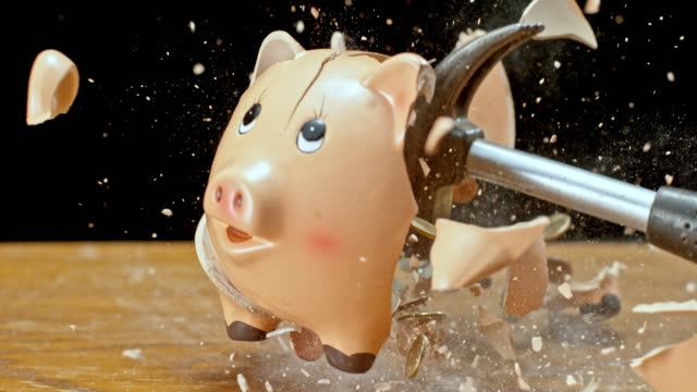 SLO MO LD Hammer smashing a piggy bank and coins flying into the air