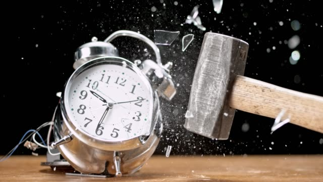 slo mo hammer smashing the two bell alarm clock ringing on the desk - clock stock videos & royalty-free footage