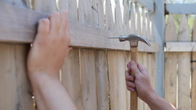 hammering nail onto wooden fence - recinzione video stock e b–roll