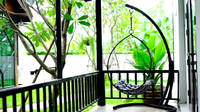 Hängemattenstuhl auf der Terrasse mit Blick auf den Garten.