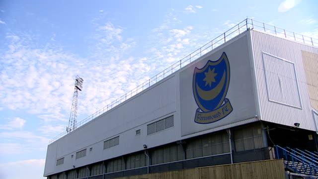vídeos de stock e filmes b-roll de portsmouth fc: ext entrance to portsmouth football club, fratton park gv fratton park flags flying over club empty ground pull focus 'portsmouth fc'... - hampshire