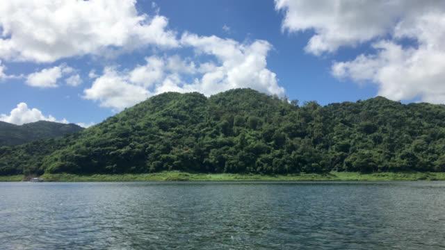 hanabanilla lake and mountains seen from a boat tour, cuba - エコツーリズム点の映像素材/bロール