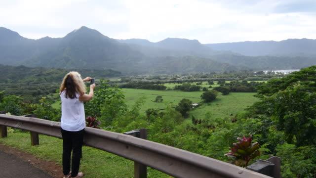 hanalei kauai hawaii woman taking video overlooking hanalei bay from above 4k - 見渡す点の映像素材/bロール
