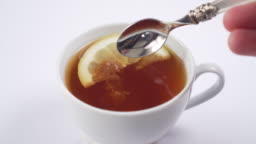 hand adds cane sugar with a dessert spoon in a cup with hot black tea