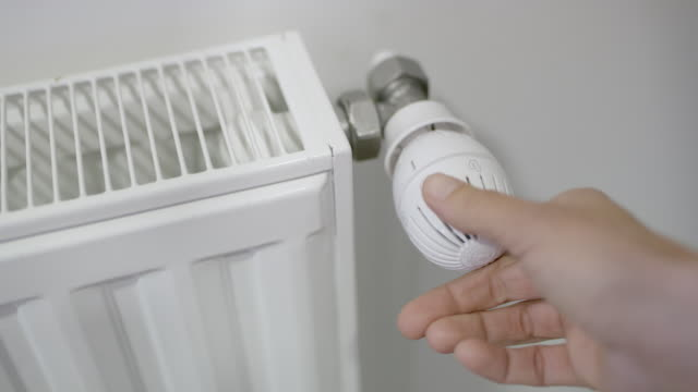 vídeos de stock, filmes e b-roll de marcador de radiador regulação cu mão - eficiência energética
