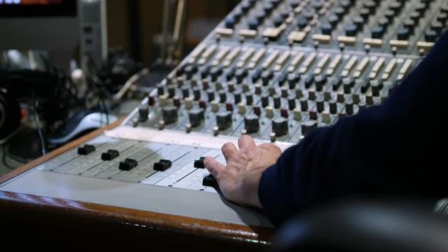 vidéos et rushes de a hand adjusts channel faders on a sound mixing desk - mixage du son