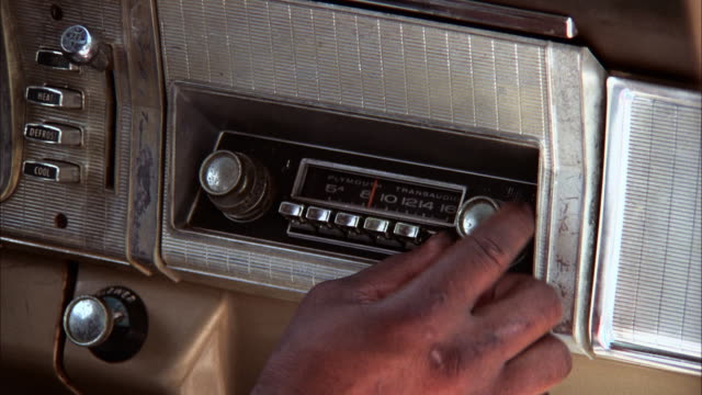 A hand adjusts the knobs on a car radio. Available in HD.