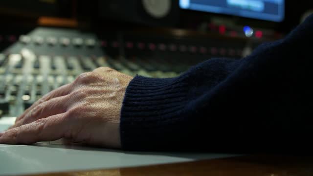 vidéos et rushes de a hand adjusts various channel faders on an audio mixing console - variété