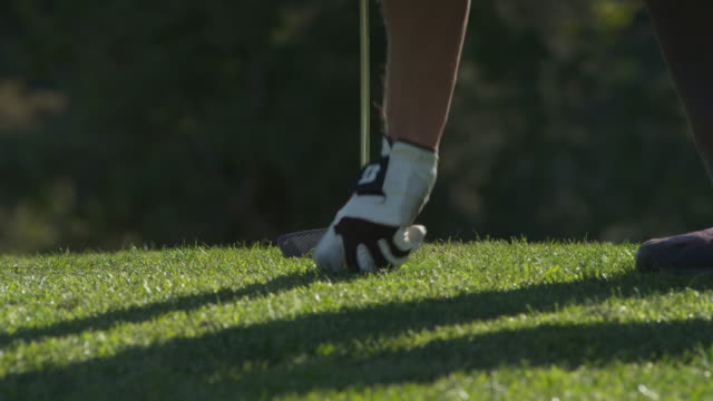 LA MS hand and feet of male golfer walking into frame, putting ball on tee and teeing off to  camera, RED R3D 4K