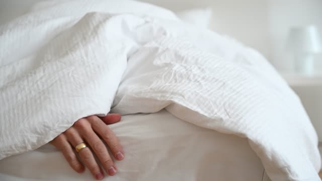 hand caressing lightly the bed under a quilt - sheet stock videos & royalty-free footage