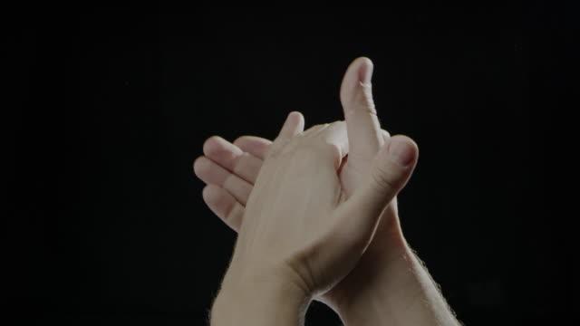 vídeos de stock, filmes e b-roll de mão branca humano palmas lenta preto fundo - idioma