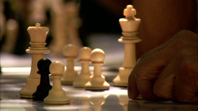 A hand cautiously moves a chess piece while the opposing player quickly moves. Available in HD.