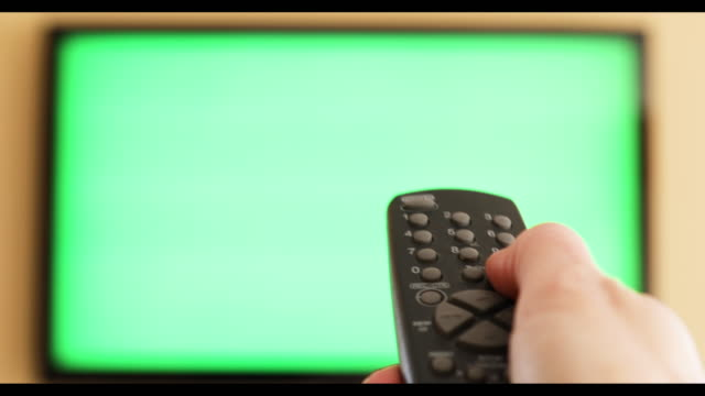 vídeos de stock e filmes b-roll de hand changing channels on green screen tv - controlo remoto