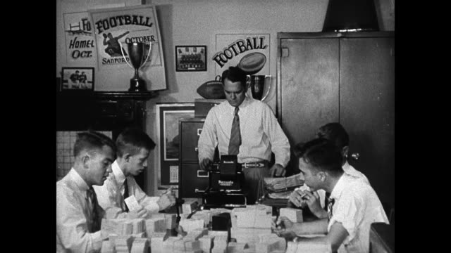 stockvideo's en b-roll-footage met hand checking batch of tickets many on table. adult male w/ college males working at table w/ tickets. ticket sales ledger. hands holding ticket... - 1936