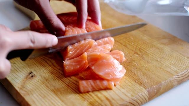 vídeos de stock e filmes b-roll de hand chef use knife slicing on fresh salmon on chopping block - salmão peixe