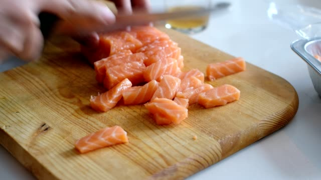 vídeos de stock e filmes b-roll de hand chef using knife slice raw salmon on wooden chopping board - marisco