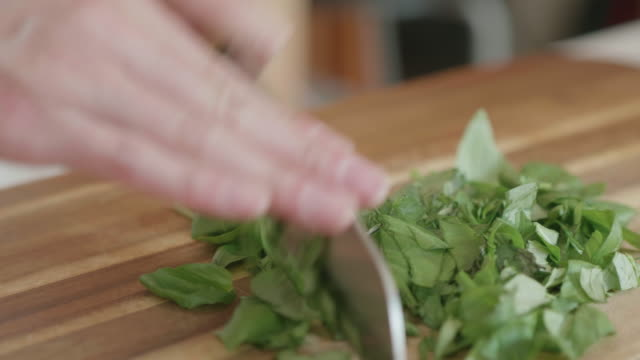 hand chopping basil leaves - basil stock videos and b-roll footage