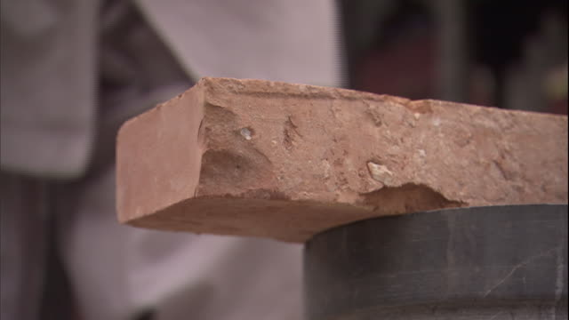 cu hand chopping brick in half/ china - ziegel stock-videos und b-roll-filmmaterial