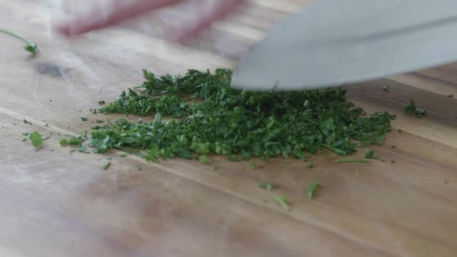 hand chopping parsley on wooden chopping board - parsley stock videos and b-roll footage