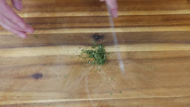 hand chopping thyme on wooden chopping board