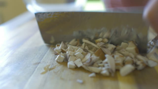 stockvideo's en b-roll-footage met hand hakken witte paddestoel op houten hakken board - paddenstoel