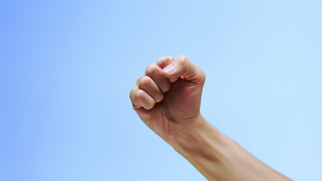 a hand clenched into a fist on a blue background - gesturing stock videos & royalty-free footage