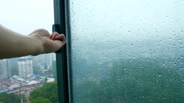 vidéos et rushes de fermez la main la fenêtre dans le jour de pluie - fermer