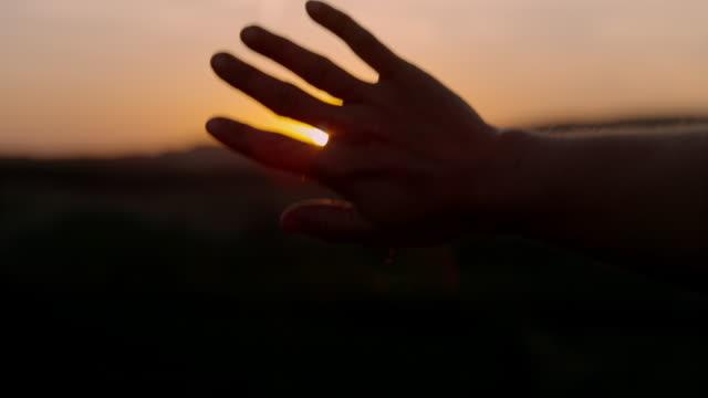 vidéos et rushes de slo mo main couvrant un coucher de soleil - gestes