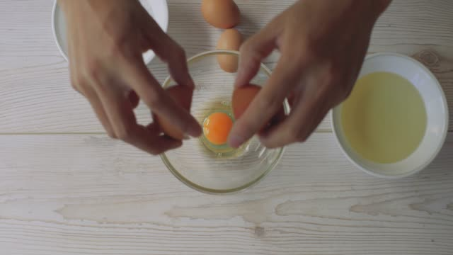 hand crack eggs into mixing bowl - cracked stock videos & royalty-free footage