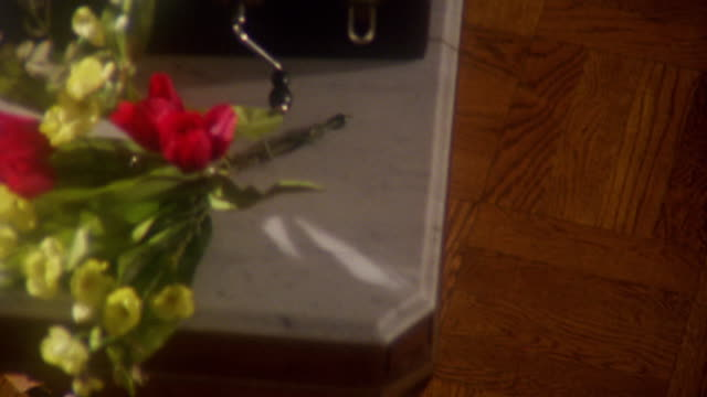 soft focus overhead pan hand cranked turntable + roses on marble topped table in ballroom - soft focus stock videos & royalty-free footage