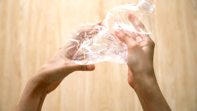 hand crushing plastic bottle. - bottiglia video stock e b–roll