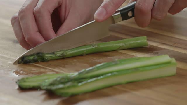 vidéos et rushes de piquées-main asperges moitié sur planche à découper en bois - couper