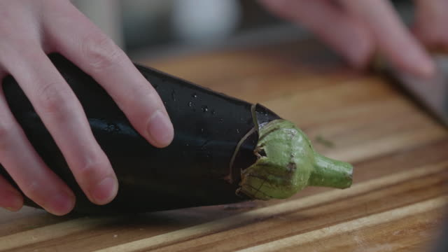 hand cut aubergine on wooden chopping board - aubergine stock videos & royalty-free footage