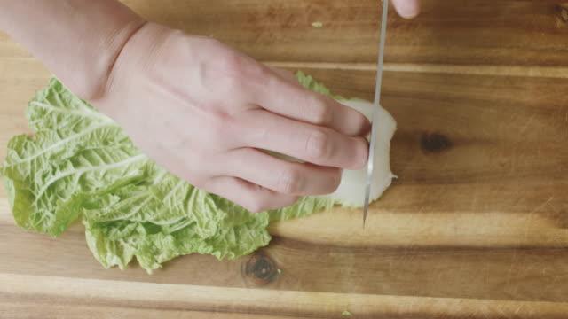 hand geschnitten chinakohl auf schneidbrett aus holz - schneiden stock-videos und b-roll-filmmaterial