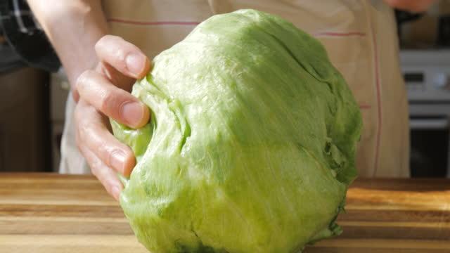 hand cut iceberg lettuce on wooden chopping board - lettuce stock videos & royalty-free footage