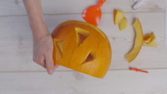 hand cut pumpkin face for halloween party - craft stock videos and b-roll footage