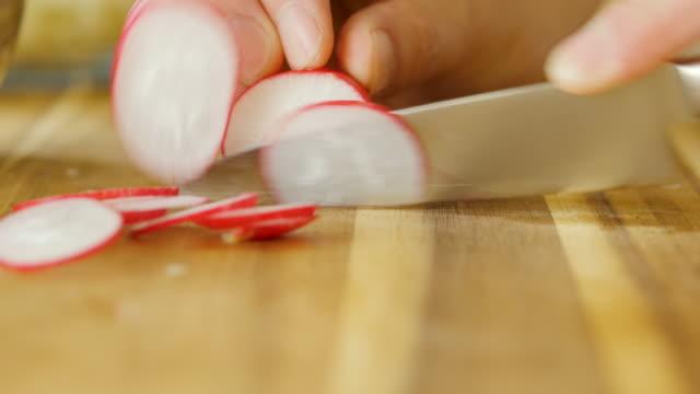 vidéos et rushes de radis coupé à la main sur la planche à découper en bois - radis